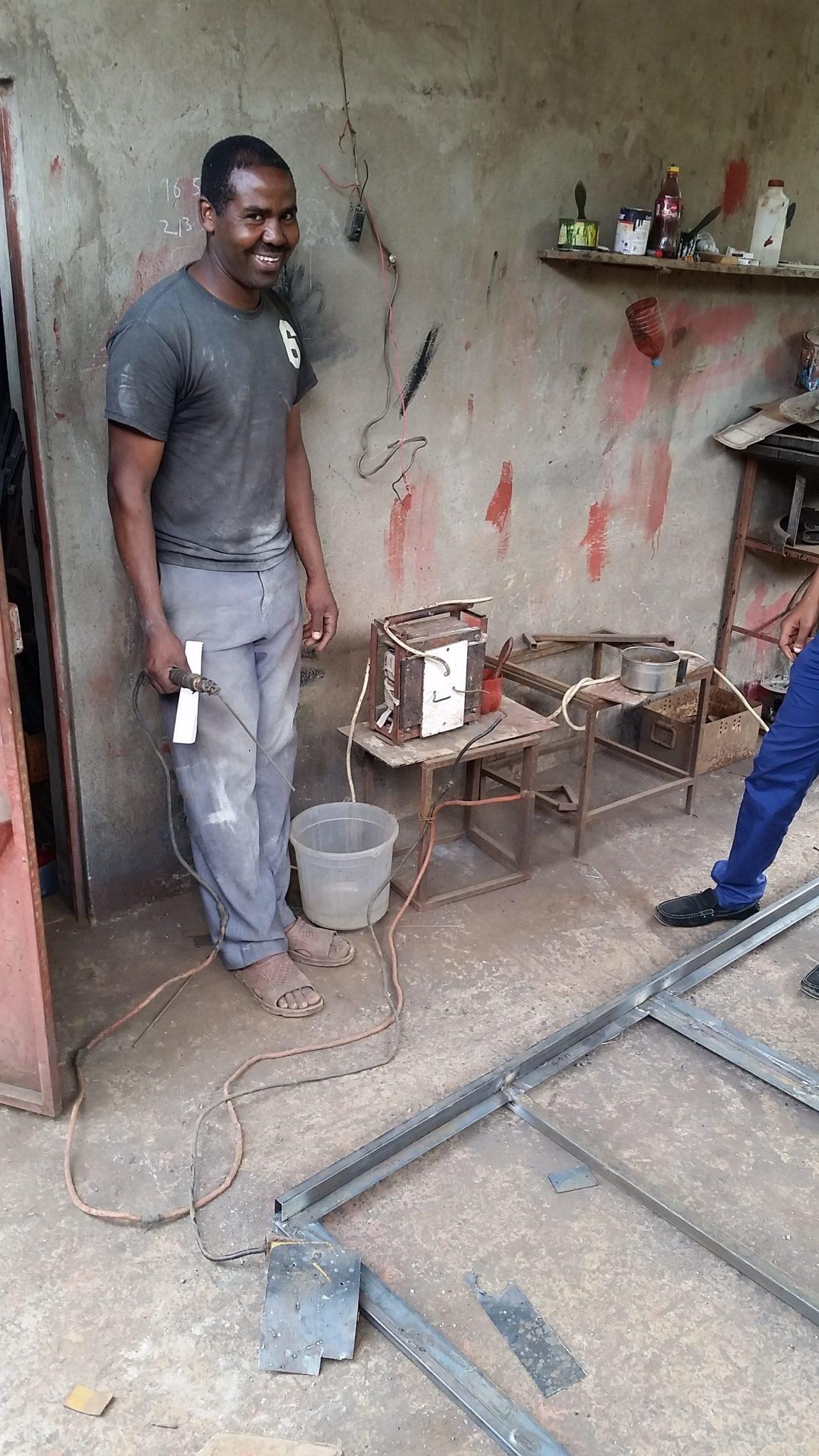 Ombeni poseert trots met zijn zelfgebouwde transformator en lasmateriaal